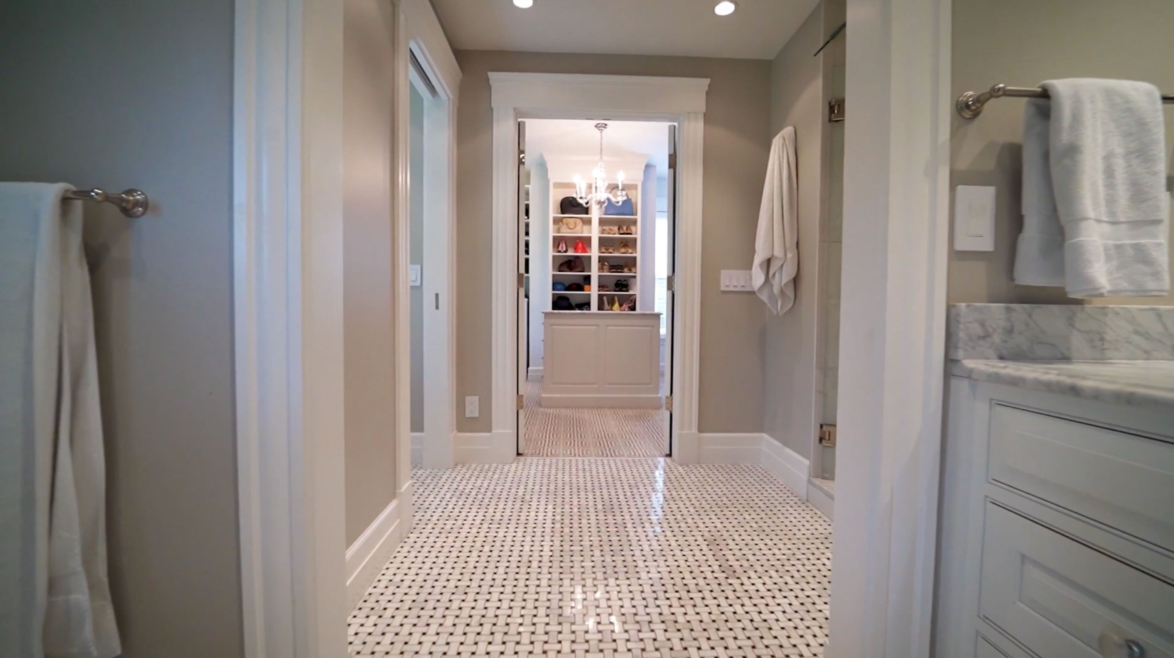 white marble bathroom with walk-in closet